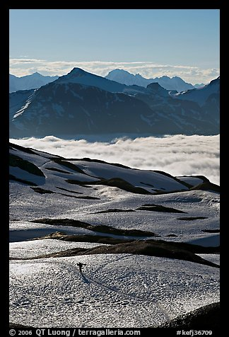Mountains and sea of clouds, hiker on snow-covered trail. Kenai Fjords National Park, Alaska, USA.