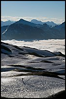 Mountains and sea of clouds, hiker on snow-covered trail. Kenai Fjords National Park ( color)