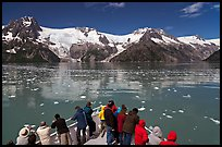 People looking at glaciers as boat crosses ice-chocked waters, Northwestern Fjord. Kenai Fjords National Park, Alaska, USA. (color)