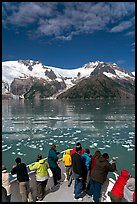 People looking as tour boat slows down for iceberg, Northwestern Fjord. Kenai Fjords National Park, Alaska, USA. (color)