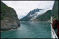 Passenger on small tour boat, island and glacier, Northwestern Fjord. Kenai Fjords National Park, Alaska, USA.