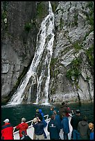 Passengers look at waterfall from tour boat, Cataract Cove, Northwestern Fjord. Kenai Fjords National Park, Alaska, USA. (color)