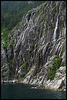 Waterfalls streaming into cove, Northwestern Fjord. Kenai Fjords National Park, Alaska, USA.