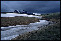 Snow nevesand mountains under dark storm clouds. Lake Clark National Park, Alaska, USA.