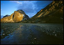 Stream on wide gravel bar and peaks at sunset. Lake Clark National Park, Alaska, USA.