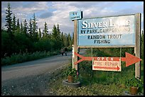 Sign and couple walking on McCarthy road near Silver Lake. Wrangell-St Elias National Park, Alaska, USA. (color)