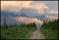 Gravel road leading to mountains lit by sunset light. Wrangell-St Elias National Park, Alaska, USA.