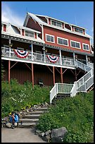 Hiker sitting on steps of Kennicott Lodge. Wrangell-St Elias National Park, Alaska, USA. (color)