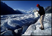 Hiker checks map on Root Glacier. Wrangell-St Elias National Park, Alaska, USA. (color)