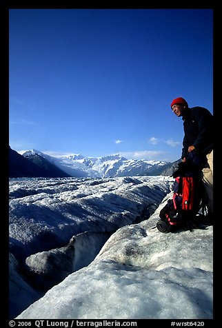 Hiker reaches for item in backpack on Root Glacier. Wrangell-St Elias National Park (color)