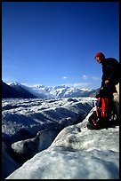 Hiker reaches for item in backpack on Root Glacier. Wrangell-St Elias National Park, Alaska, USA.