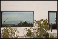 Shrubs, Chisos mountains, Persimmon Gap Visitor Center window reflexion. Big Bend National Park, Texas, USA. (color)