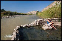 Visitor sitting in hot springs next to river. Big Bend National Park, Texas, USA. (color)