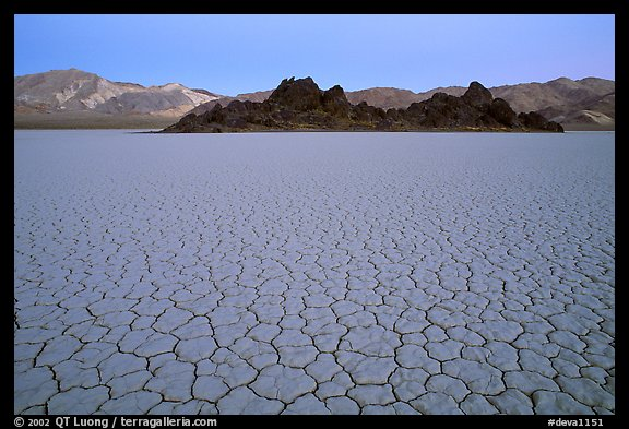 Tiles in cracked mud and Grand Stand, Racetrack playa, dusk. Death Valley National Park, California, USA.