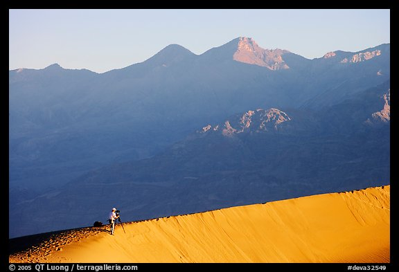 Photographer on dune ridge at sunrise. Death Valley National Park (color)