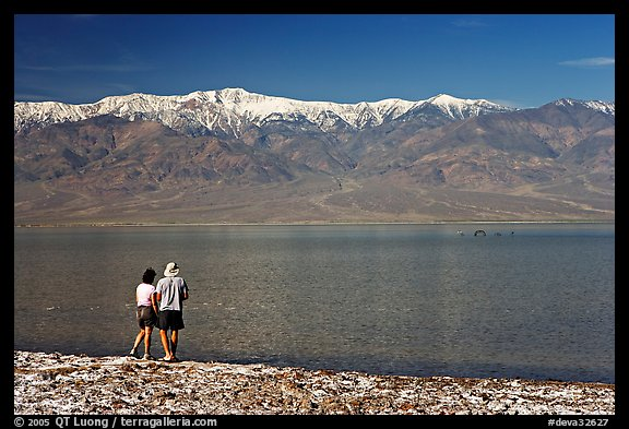 Couple watches the dragon in ephemeral lake. Death Valley National Park, California, USA.