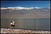 Couple watches the dragon in ephemeral lake. Death Valley National Park, California, USA. (color)