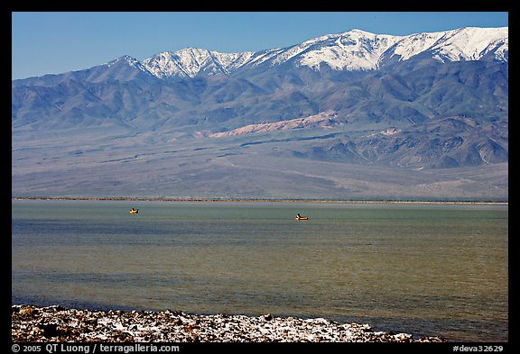 Kayakers in ephemeral Manly lake, and Panamint Range. Death Valley National Park, California, USA.