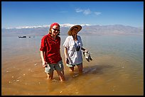 Women wading in the knee-deep seasonal lake. Death Valley National Park, California, USA.