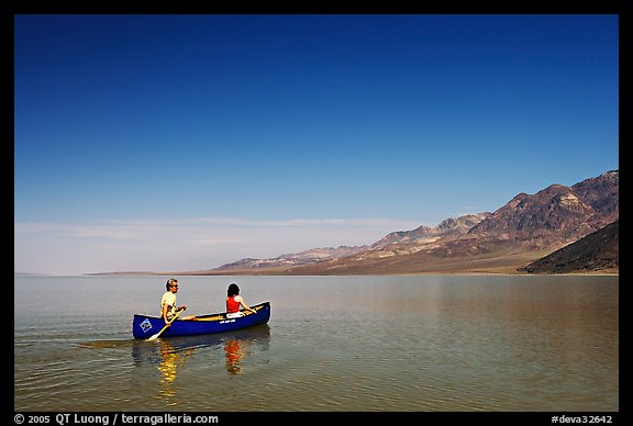 Canoeing on the ephemerald Manly Lake with Black Mountains in the background. Death Valley National Park, California, USA.
