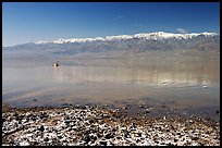 Salt formations, kayaker in a distance, and Panamint range. Death Valley National Park, California, USA.