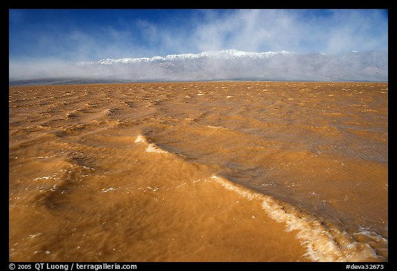 Extremely rare waves on mud-colored Manly Lake, early morning. Death Valley National Park, California, USA.
