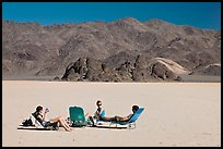 Visitors sunning themselves with beach chairs on the Racetrack. Death Valley National Park, California, USA.