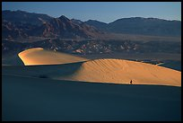 Hiker on ridge, Mesquite Dunes, sunrise. Death Valley National Park, California, USA. (color)