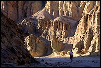 Hikers surrounded by tall walls in Golden Canyon. Death Valley National Park, California, USA. (color)