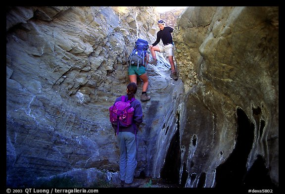 Hikers climbing in a narrow side canyon. Death Valley National Park (color)