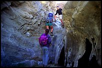 Hikers climbing in a narrow side canyon. Death Valley National Park, California, USA. (color)