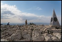Hiker sitting on Guadalupe Peak summit with cairn and monument. Guadalupe Mountains National Park, Texas, USA. (color)