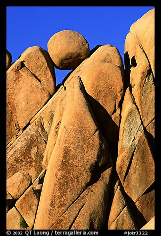 Spherical boulder jammed on top of triangular boulders, Jumbo rocks. Joshua Tree National Park, California, USA.