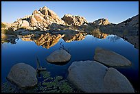 Rockpiles reflected in pond, Barker Dam, sunrise. Joshua Tree National Park, California, USA.