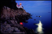 Bass Harbor lighthouse by night with moon reflection in ocean. Acadia National Park, Maine, USA.