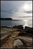Rock slabs and sun over ocean, Schoodic Peninsula. Acadia National Park, Maine, USA.