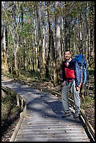 Hiker with backpack standing on boardwalk. Congaree National Park, South Carolina, USA.