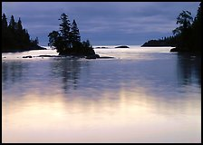 Islet and bright sky reflected in water below dark clouds. Isle Royale National Park ( color)