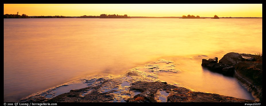 Lakeshore and glassy water painted yellow by sunrise. Voyageurs National Park (color)