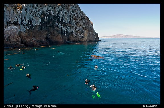 Divers, emerald waters, and steep cliffs, Annacapa island. Channel Islands National Park (color)
