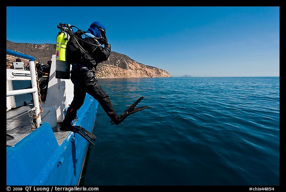Scuba diver stepping out of boat, Santa Cruz Island. Channel Islands National Park, California, USA.