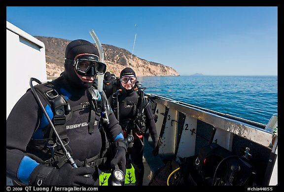 Scuba divers in wetsuits ready to dive from boat, Santa Cruz Island. Channel Islands National Park, California, USA.
