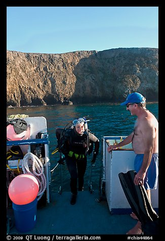 Woman diver stepping onto boat and Annacapa Island. Channel Islands National Park (color)