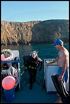 Woman diver stepping onto boat and Annacapa Island. Channel Islands National Park, California, USA.