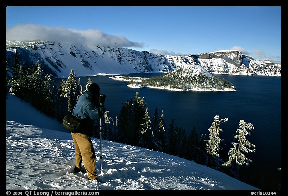 Photographer on  rim of  Lake in winter. Crater Lake National Park, Oregon, USA.
