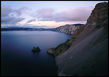 Caldera slopes and Phantom ship at dusk. Crater Lake National Park, Oregon, USA.