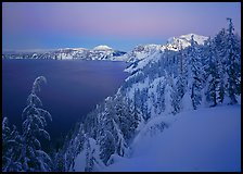 Snow-covered rim and trees, lake and mountains, dusk. Crater Lake National Park, Oregon, USA.