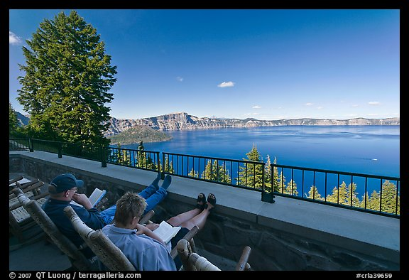 Reading on Crater Lake Lodge Terrace overlooking  Lake. Crater Lake National Park, Oregon, USA.
