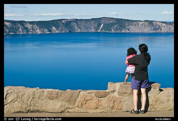 Woman and baby looking at Crater Lake. Crater Lake National Park, Oregon, USA.