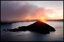Sun rising behind Wizard Island. Crater Lake National Park, Oregon, USA.
